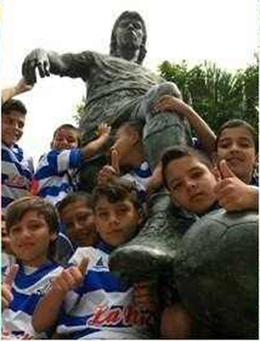 小孩子在埃斯科巴的雕塑下竖起大拇指
