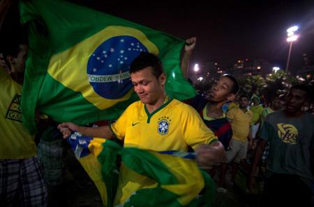 一名在海滩上看球的巴西球迷面带微笑撕毁巴西国国旗