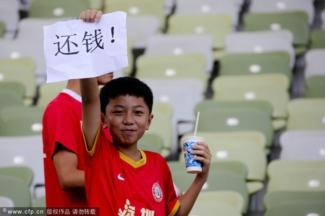 """球场的孩子也在为球员举着""""还钱""""标语"""